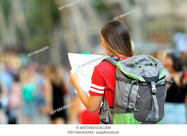 Back view of a teen tourist searching location in a paper map on the street