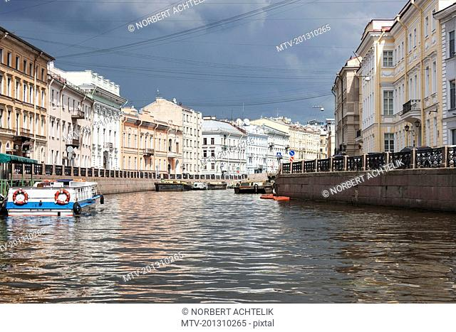 Boats moored in canal amidst buildings in city, Russia