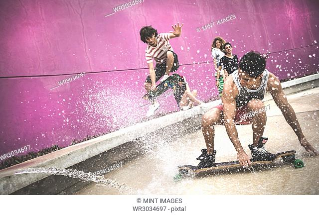 A skateboarder crouching down to skate through water