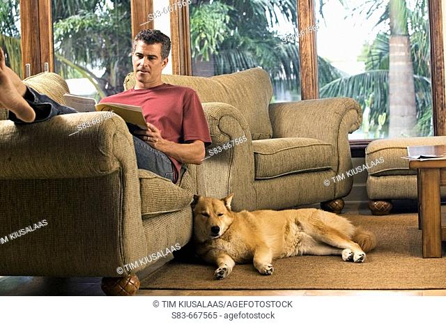 Man reading on chair with dogs sleeping on floor next to him