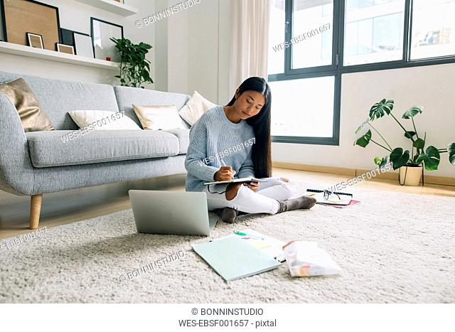 Young woman sitting on floor in the living room writing down something