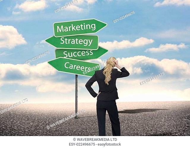 Businesswoman looking at signposts with marketing term with bright blue sky