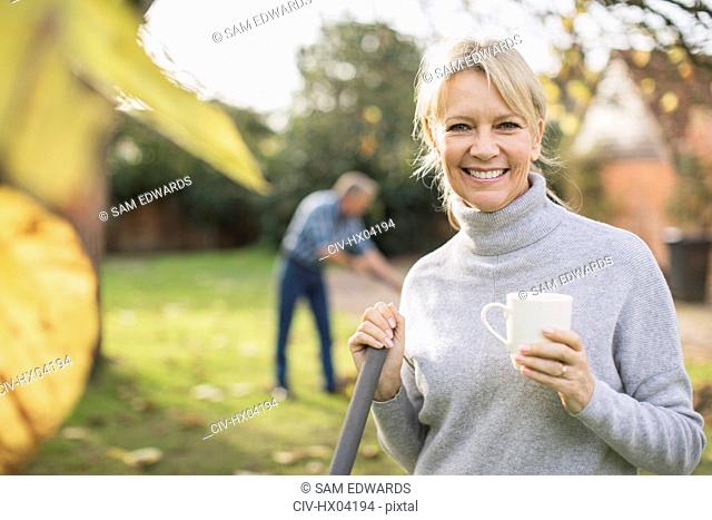 Portrait smiling, confident mature woman drinking coffee and raking autumn leaves in backyard