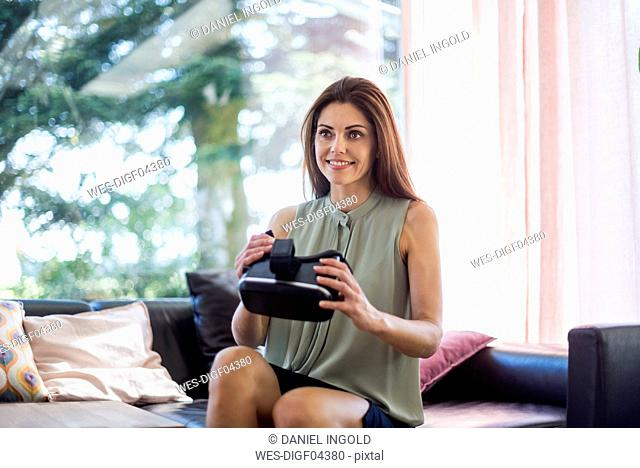 Smiling woman sitting on couch at home holding VR glasses