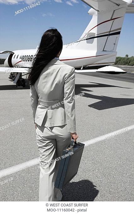 Mid-adult businesswoman walking towards private jet