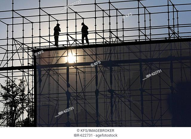 Two men installing a huge open-air screen, Djemaa el-Fna, Marrakech, Morocco, Africa
