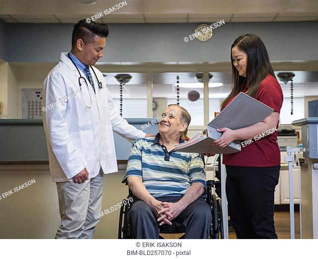 Doctor comforting patient in wheelchair