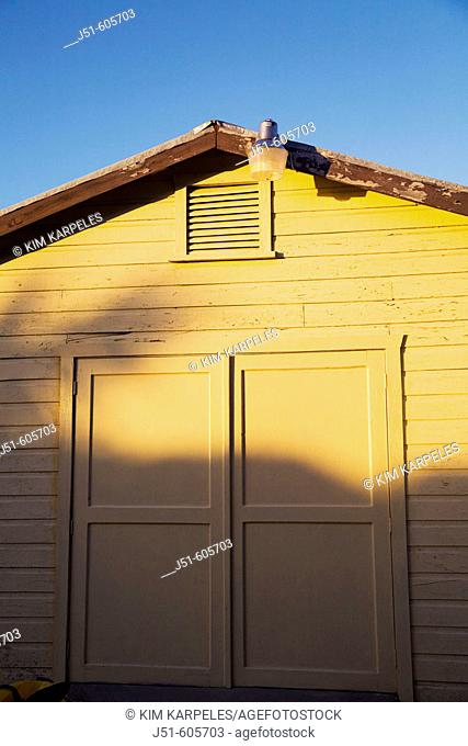 BELIZE Ambergris Caye   Exterior of yellow wooden building in late afternoon, closed wooden doors