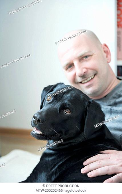Portrait of man with his dog, smiling