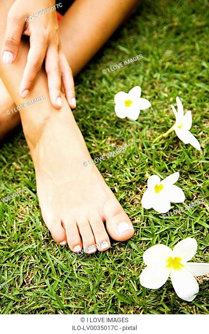 Close up shot of a woman's feet in a tropical setting with frangipani