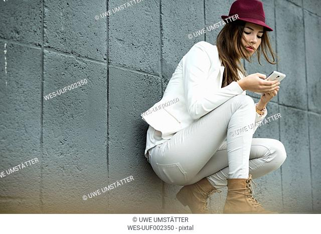 Young woman with hat looking at her smartphone in front of grey wall