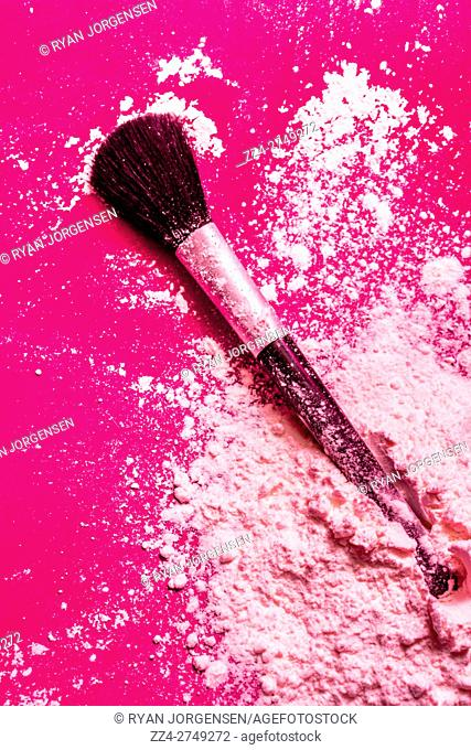 Cosmetics powder fine art still life with pink blusher or foundation scattered on a bright vivid pink background with a large soft brush or applicator