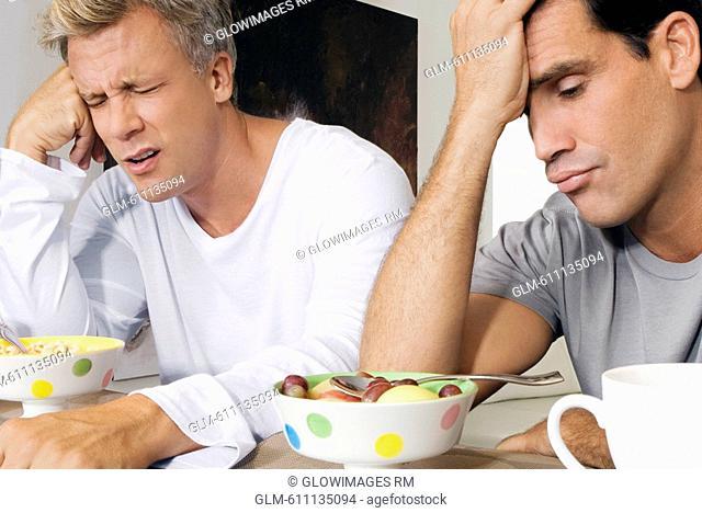 Men frowning at bowls of cereal and fruits