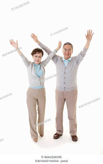 Senior man and woman standing with arms outstretched