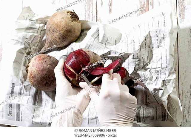 Woman with rubber gloves peeling beetroot
