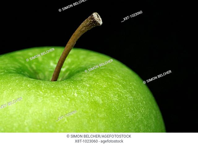 Close Up of a Granny Smith Apple Agianst a Black Background