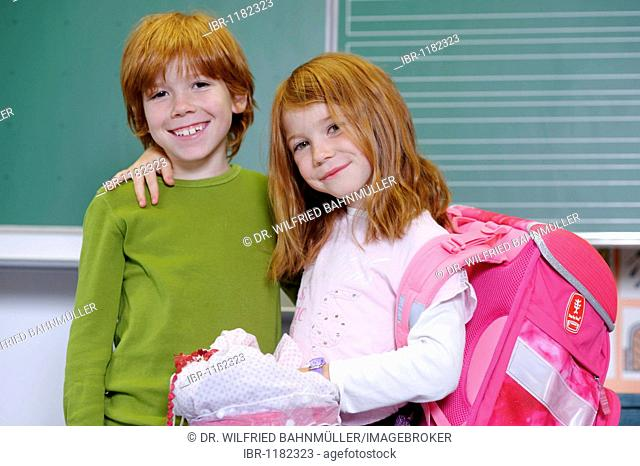 Two children in primary school, friends or siblings in a classroom