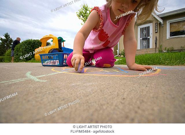 Little Girl Drawing on the Sidewalk with Chalk in the Summer