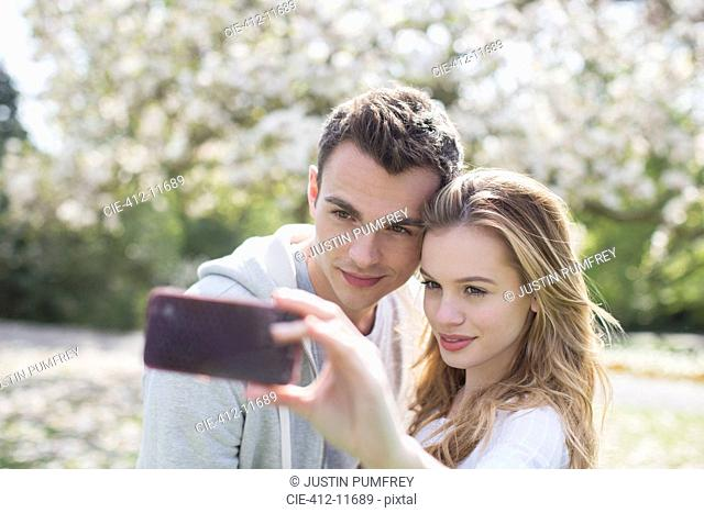 Couple taking self-portrait in park