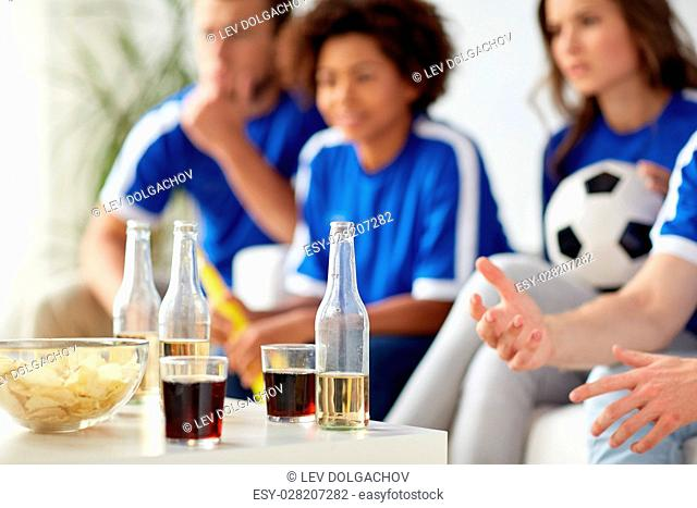 friendship, sport and entertainment concept - football or soccer fans with drinks and chips at home