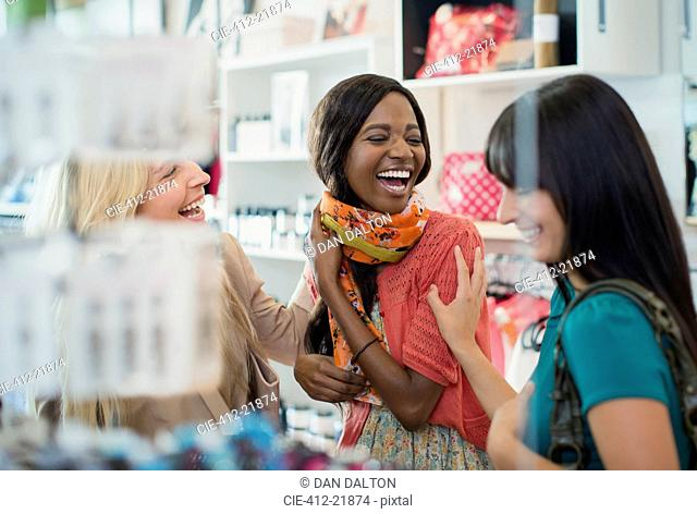 Women laughing together in clothing store