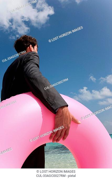 Businessman carrying inner tube on beach