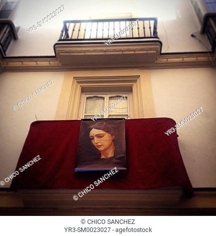An image of the Virgin Mary and a red carpet covers a balcony during Easter Holy Week in Cadiz, Andalusia, Spain