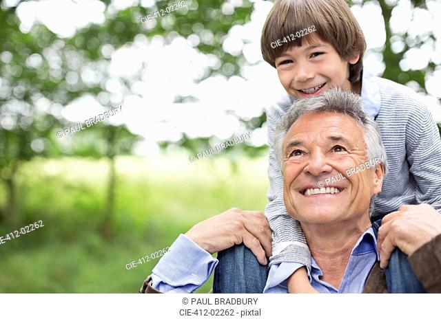 Man carrying grandson on his shoulders