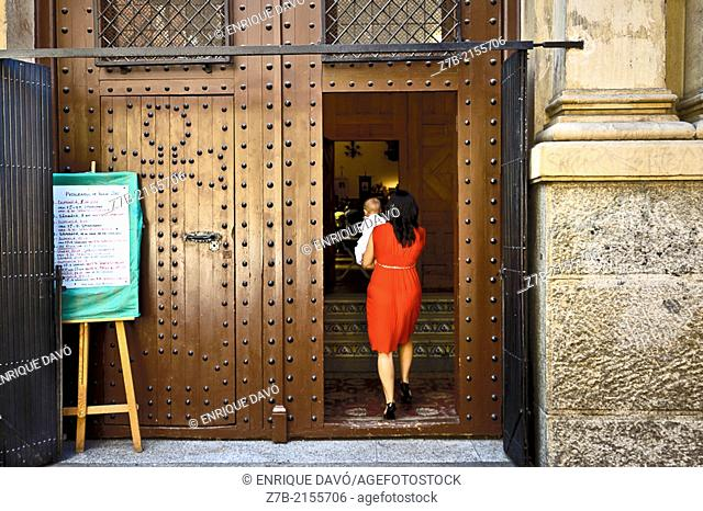 A woman with a red dress in the entrance of a church of Madrid city, Spain