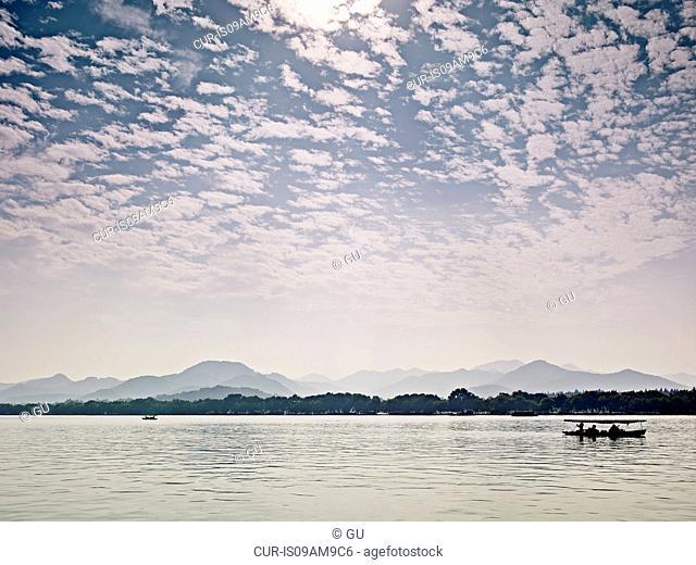 Silhouetted fishing boat on West Lake, Hangzhou, Zhejiang, China