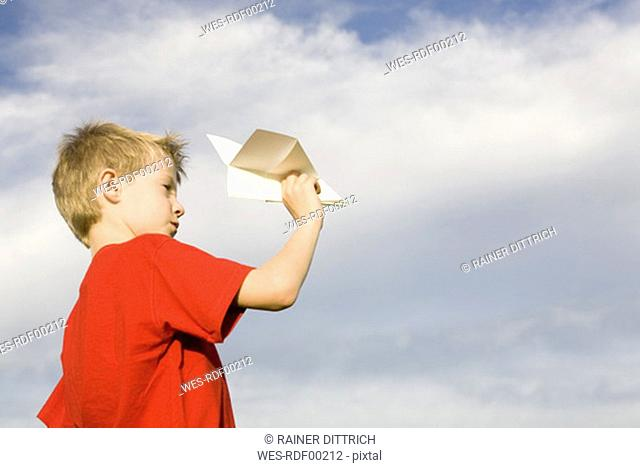 Boy 10-12 holding paper plane, side view