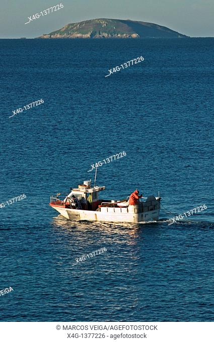 Fishing boat in front of Punta Paxariñas with Onza island on the background. Pontevedra, Galicia, Spain