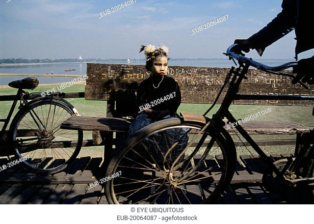 Young girl with face decorated with leaf patterns sitting on wooden bench on U-Bein bridge with wheels of passing cyclist in the foreground