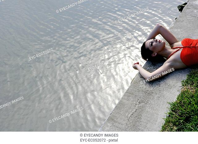 Woman lying on the ground near water