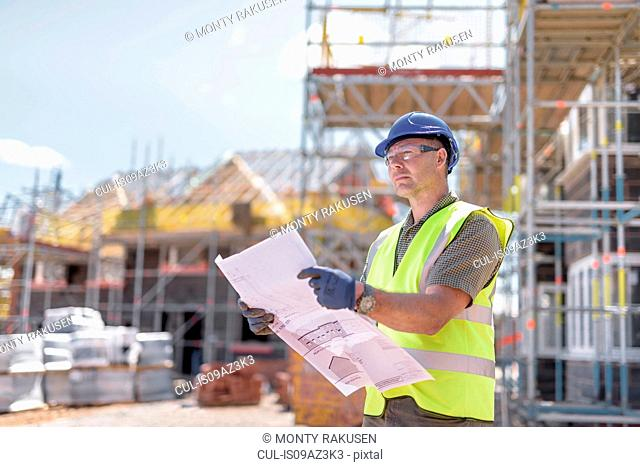 Site manager looking at plans on housing building site