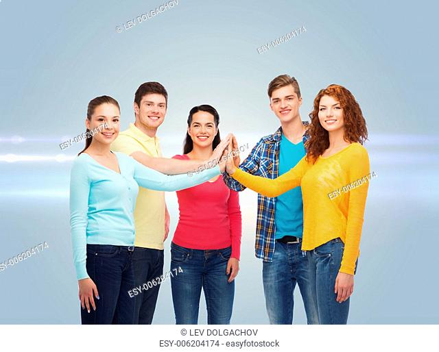 friendship, teamwork, gesture and people concept - group of smiling teenagers making high five over gray background with laser light