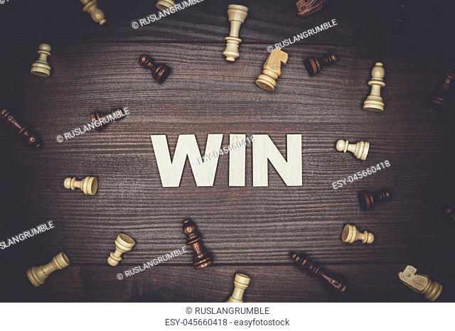 word win and chessmen on the brown wooden background