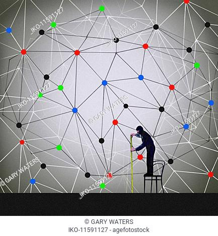 Man standing on chair measuring complex network pattern with tape measure