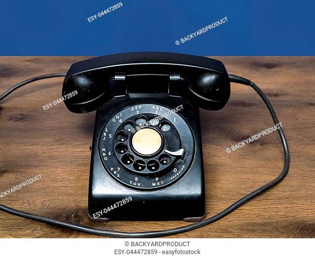 Old and antique rotary telephone on wooden desk with blue background