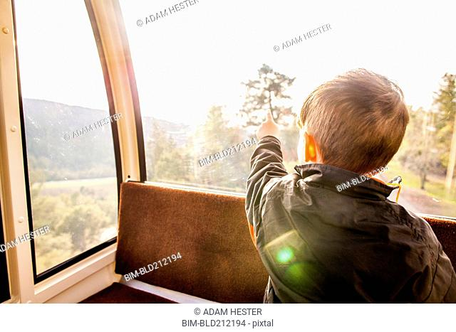 Caucasian boy looking out tram window