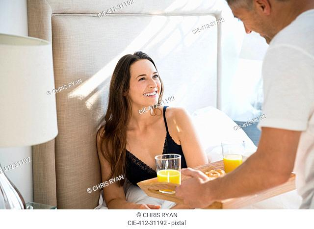 Wife smiling at husband serving breakfast in bed