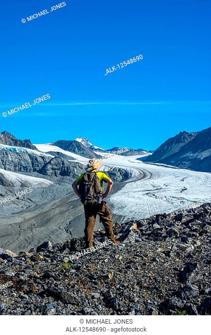 A man walks in Gulkana Glacier Valley in the Eastern Alaska Range in South-central Alaska on a sunny summer afternoon; Alaska, United States of America