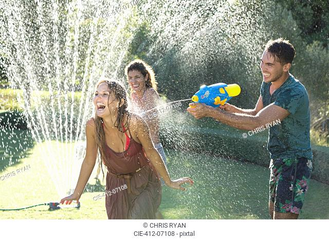 Friends playing with water guns in sprinkler in backyard