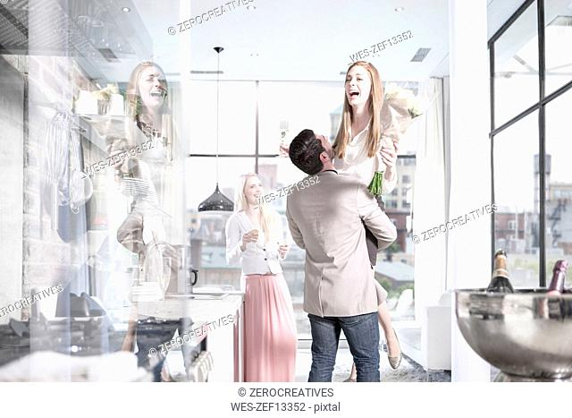 Man lifting up laughing woman in apartment with city view