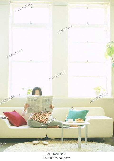 Woman reading newspaper on sofa