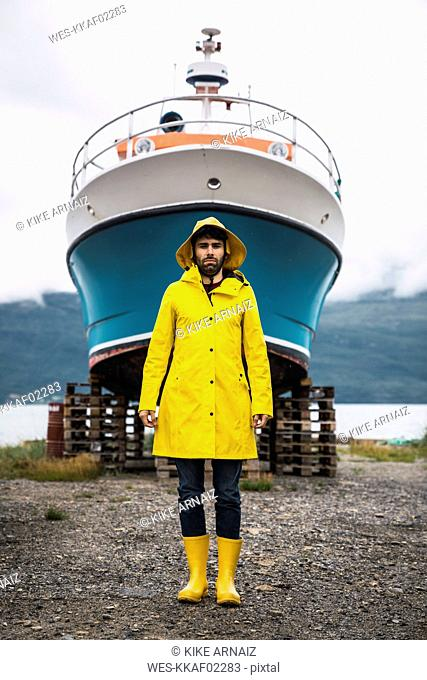 Young man standing in front of a ship, wearing rain clothes, Lapland, Norway