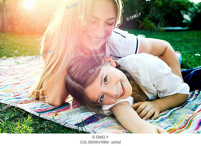 Mother and daughter lying on rug in garden