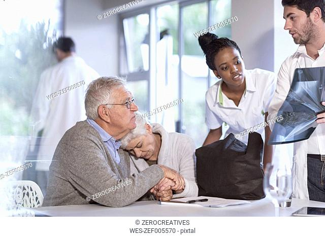 Sad senior woman with husband at clinic talking to doctor and nurse