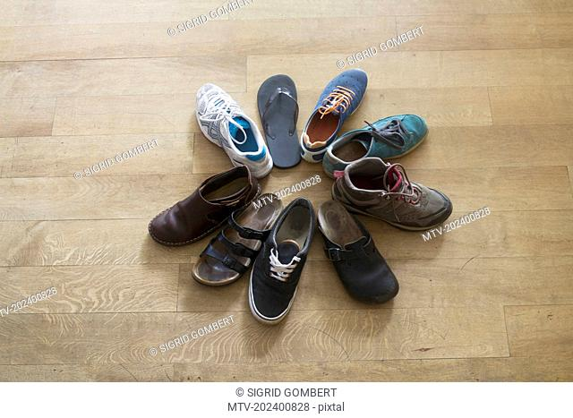 Shoes in form of a circle on wooden floor