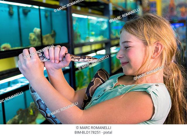 Caucasian girl admiring snake in pet store